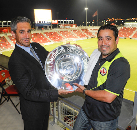 Jose Lizardo (right) and Brian Melekian, COO of the NASL, pose with the Silverback's newest trophy