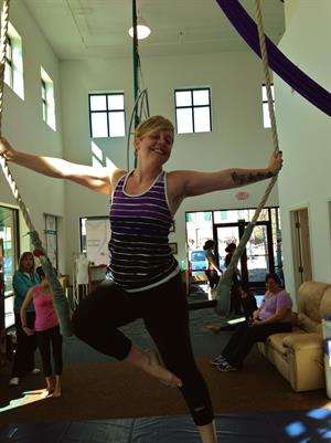 The author poses on a trapeze at Sky Gym