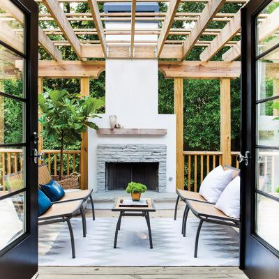 French doors in the kitchen open to an outdoor seating area with a fireplace and covered pergola.