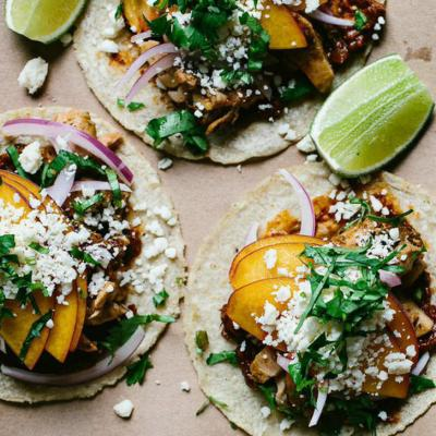 Charcoal-grilled chicken taco with Pasilla de Oaxaca, lime pickled onion, cotija, and peach