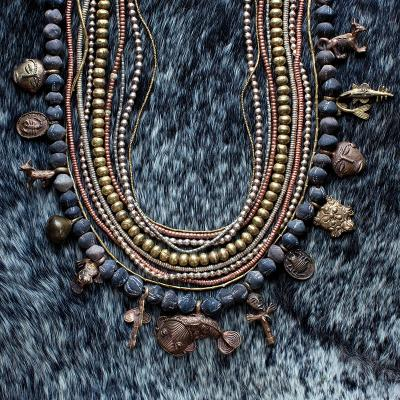 Charms, hand-molded clay beads, and metal strands from West Africa, $400 for the cluster; calf-hair clutch, $250