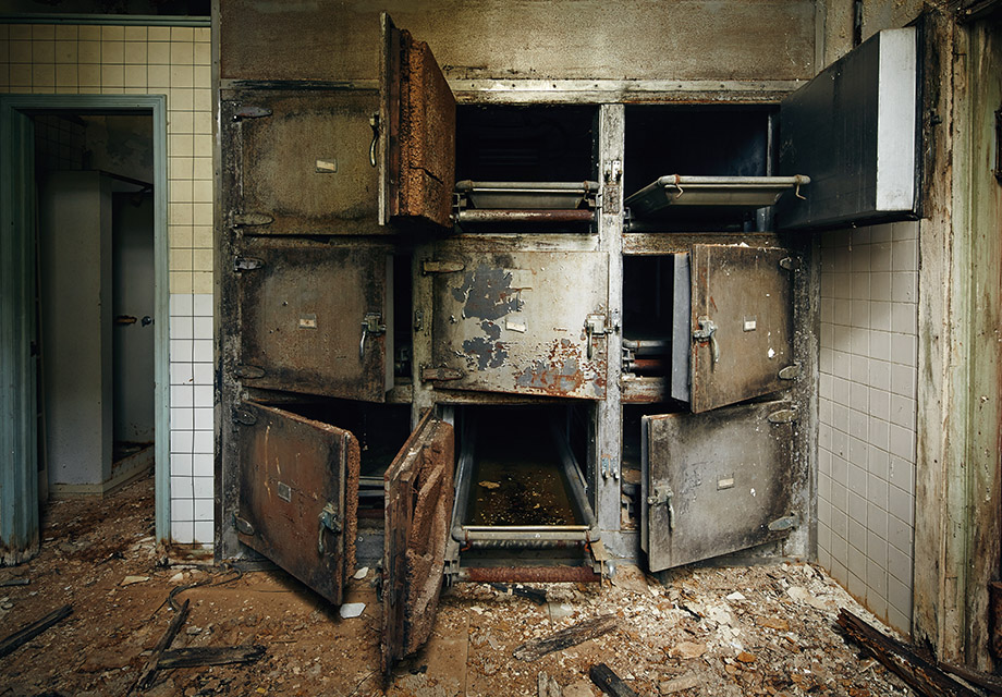 Morgue drawers sealed with iron doors once held the corpses of patients in the basement of the Jones Building. Today the building is collapsing from the top down, and falling debris covers the morgue floor.