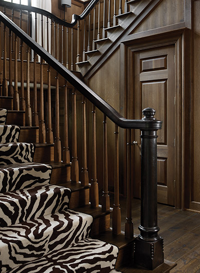 """The staircase's newel post, handrails, and pickets were all custom-designed and carved, then ebonized and fumed rather than painted. The silky finish comes from a heavy coat of Briwax. The flooring consists of 10-inch-wide oak planks in a custom stain. Neely insisted that each board be at least 10 feet long to imply old growth. Wide, short planks look like a """"checkerboard,"""" he says."""