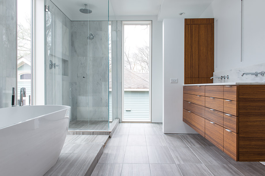 Tall glass panels flood the bathroom with daylight in the bell designed home