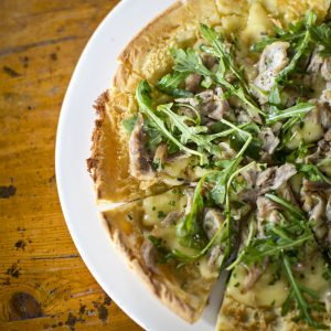 Confit Duck Dutch Baby Flatbread with robiola cheese, arugula, and lavender-infused honey