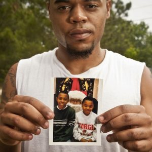 Sha'von Patterson holding a photo of him and his brother Justin