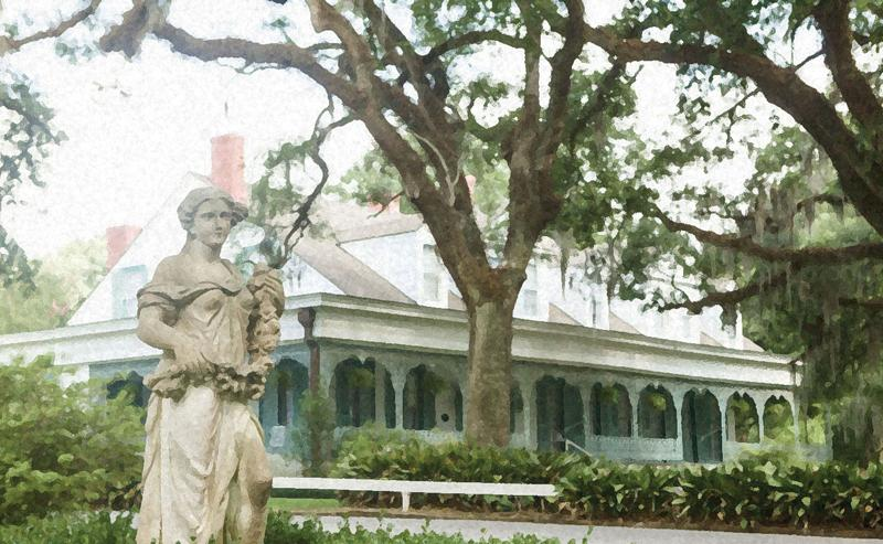 Centuries-old live oak trees front the wraparound veranda, featuring ornate ironwork and a row of rocking chairs.