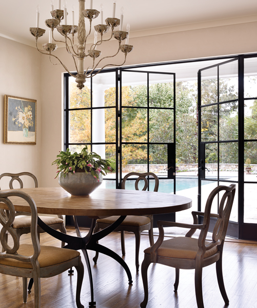 The metal base on the breakfast room's Caine dining table by Beau Studio echoes the dramatic metal windows. The painting is by Bill's cousin Lulie Wallace.