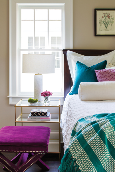 Pops of jewel tones in the master bedroom illustrate how the overall neutral palette throughout the house can become the backdrop for multiple color schemes.