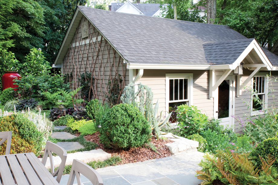 Garden designer Matthew Klyn added a door and windows to the side of the garage facing the house to disguise it as a cottage. A kalmia wood trellis adds texture to another side.
