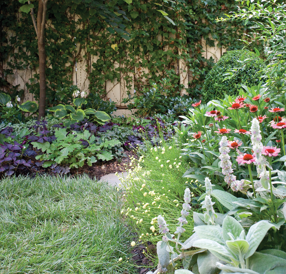 An unnecessary concrete driveway on the side of the house was replaced with stepping-stones that wander past flower beds filled with colorful perennials.