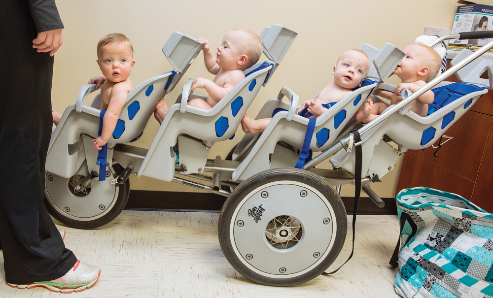 Julianne makes a rare solo trip with all four babies for their doctor's appointment. The quads wait their turns in the Kirklands' industrial- sized stroller and are moved through the checkup—which takes one physician and multiple nurses to complete—like parts in an assembly line.