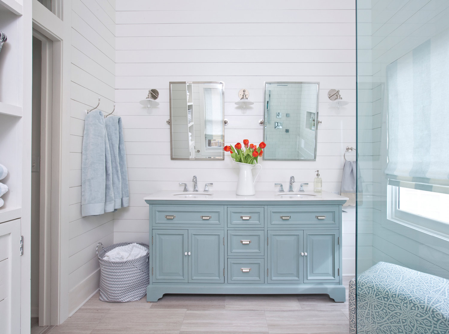"""""""The aqua color on the vanity and barn doors is very serene, while the white walls keep things fresh,"""" says designer Lisa Gabrielson."""
