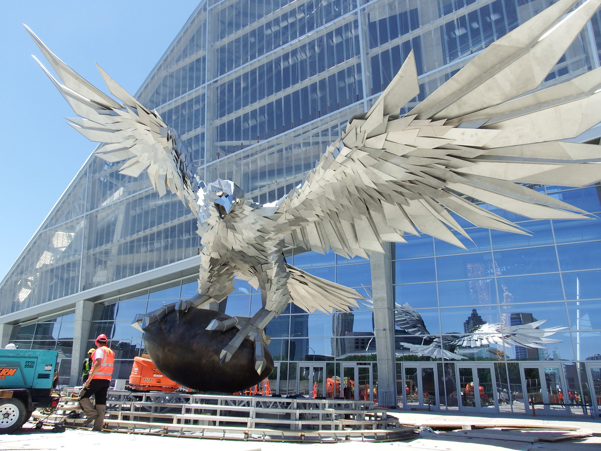 A giant stainless steel falcon is rising up in front of for Mercedes benz dealer atlanta
