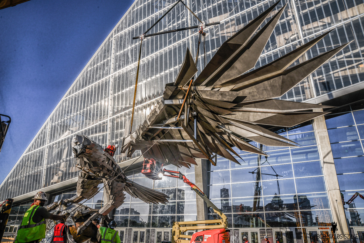 A giant stainless steel falcon is rising up in front of for Mercedes benz arena atlanta