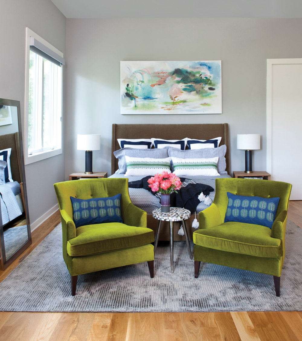 Green velvet chairs in front of the master bed