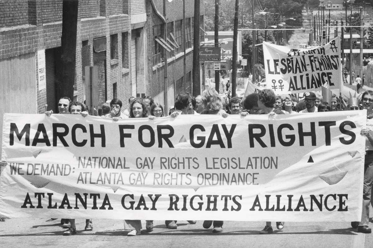 """Protesters march in downtown Atlanta holding a """"March for gay rights"""" sign"""