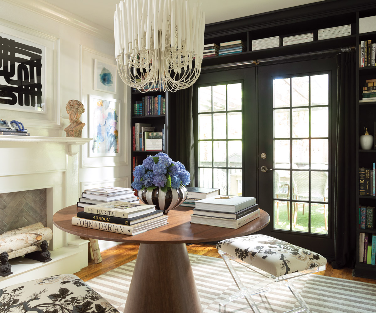 A beautifully sun-lit room with a chandelier and book shelf