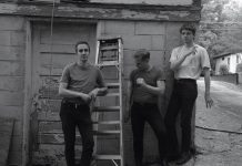 Band members stand in an alleyway in a neighborhood