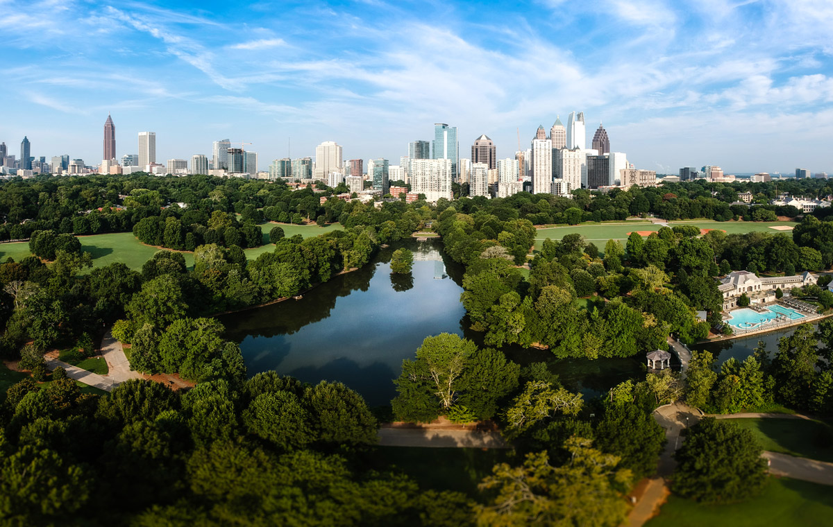 City skyline of Atlanta with Piedmont Park and the lake in the morning sun
