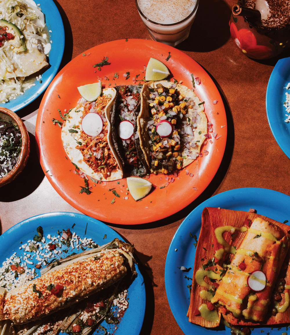 Three garnished tacos and other Mexican food spread on a table