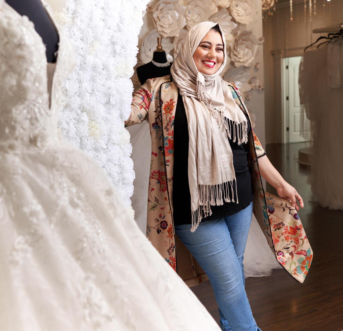 Rawan Asad standing next to a wedding gown