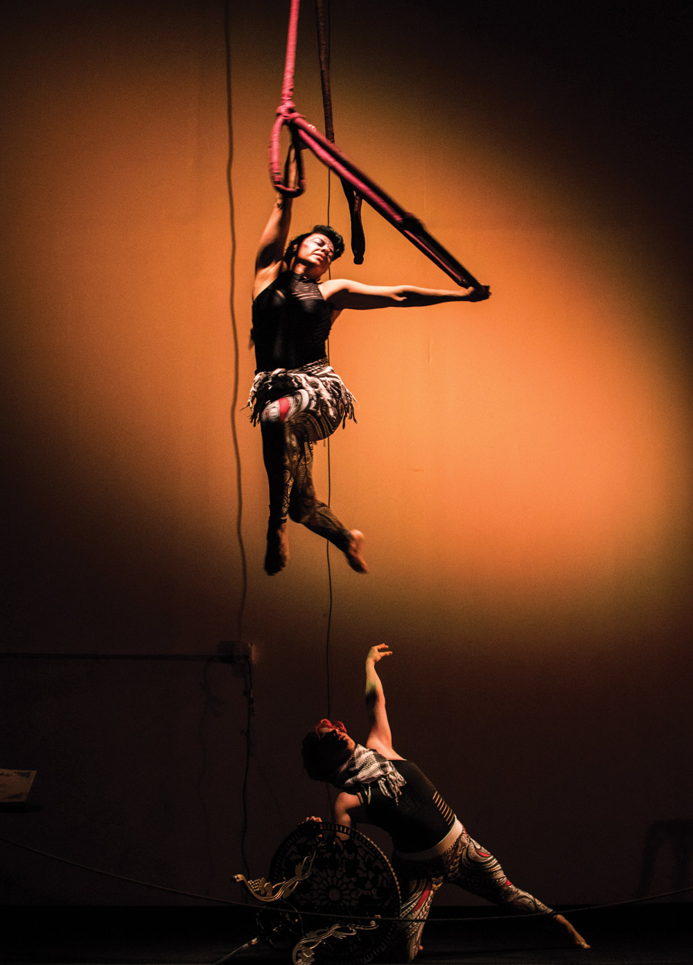 Performers hanging from the ceiling during an aerial silk routine