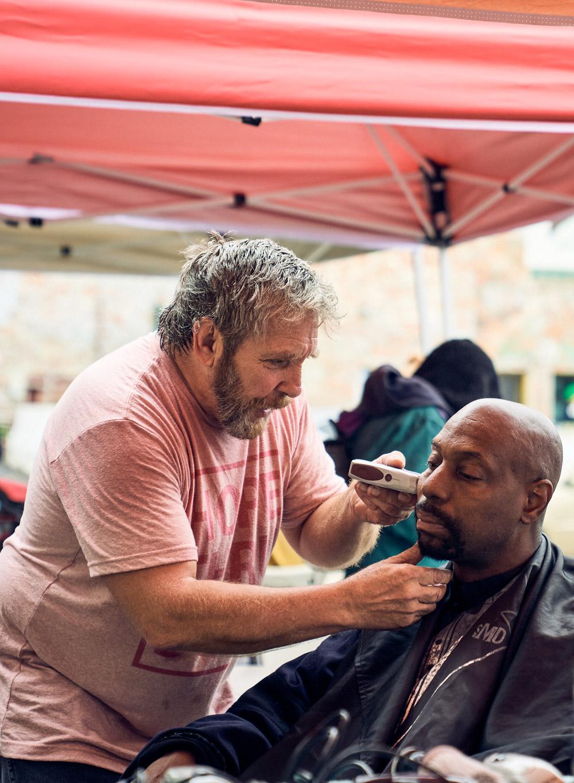 A man giving a haircute to a homeless man