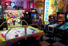 An arcade room with a Pac Man game, air hocky, pinball machines, and more