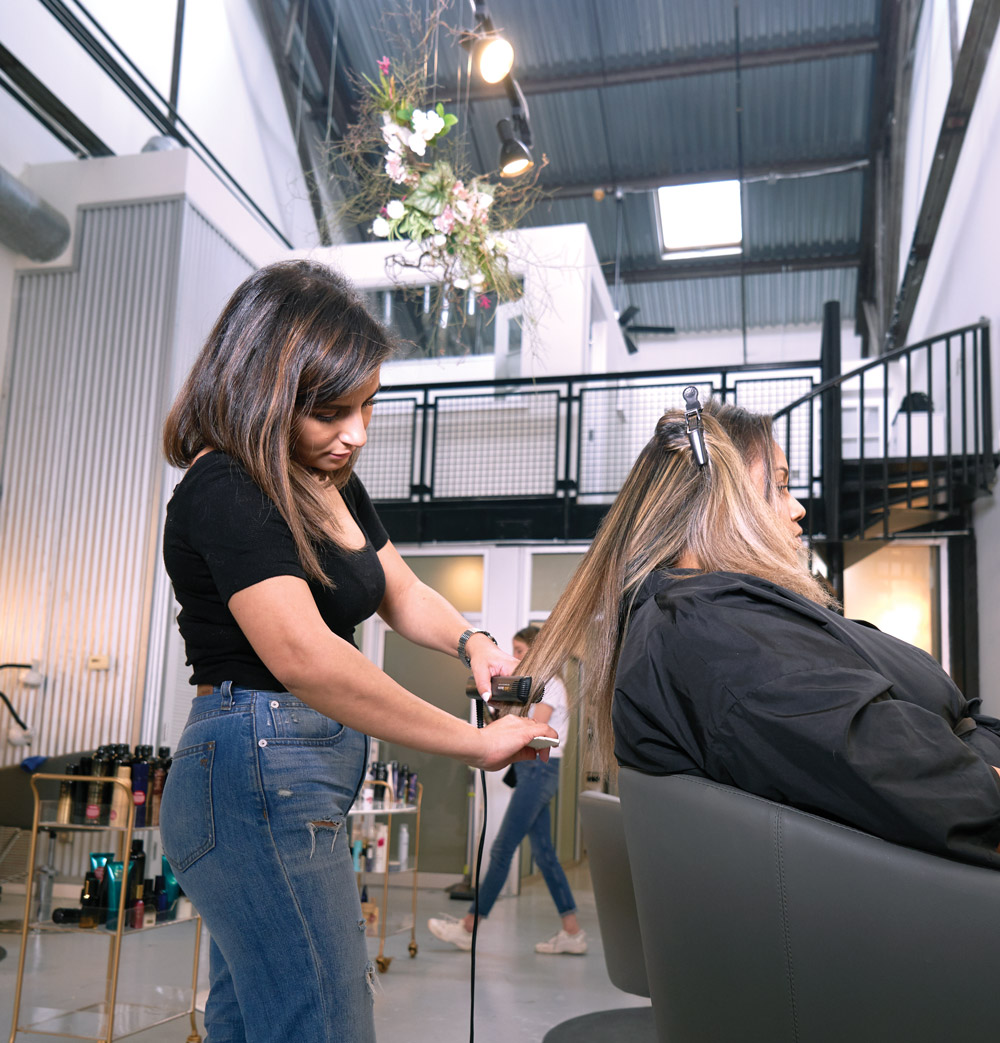 A hairstylist cuts another woman's hair