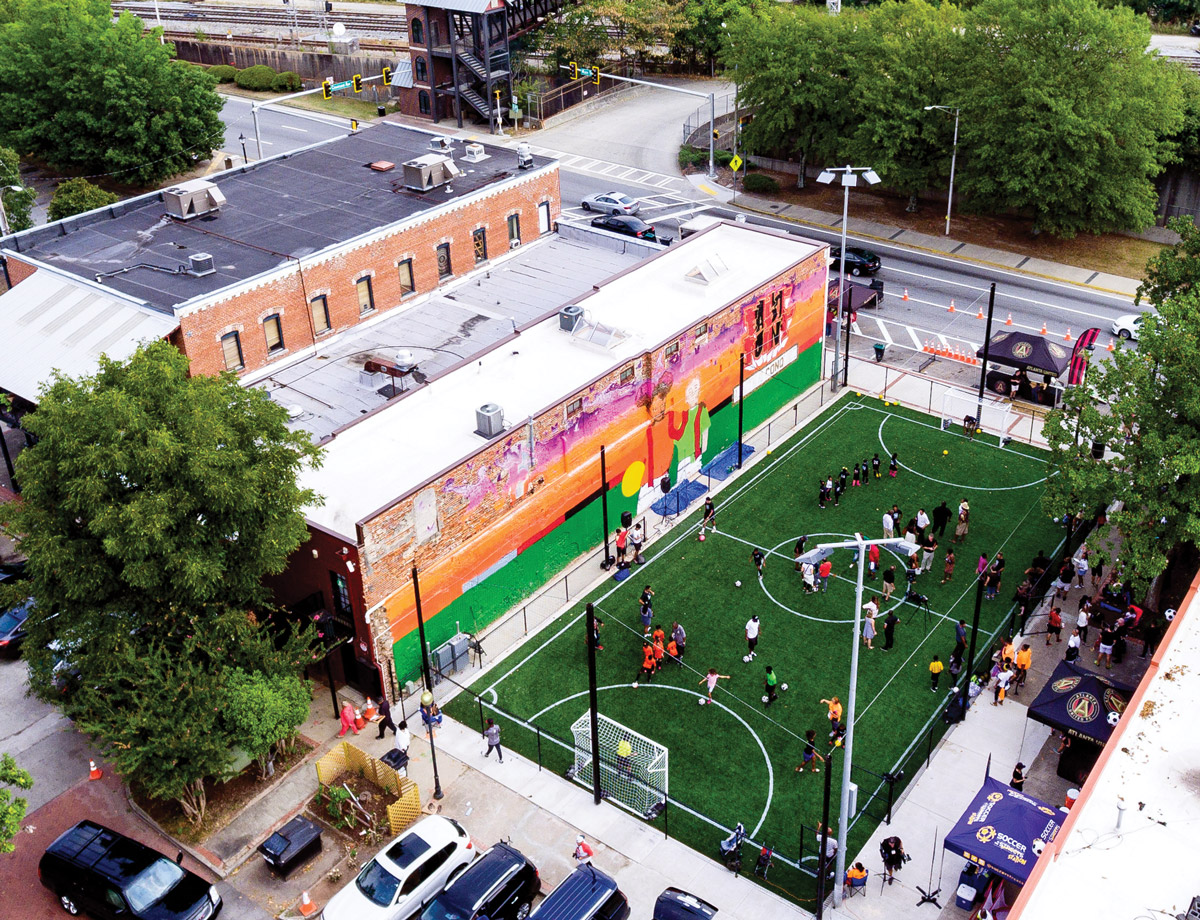 An overhead shot of kids playing soccer on a field across from the East Point MARTA station