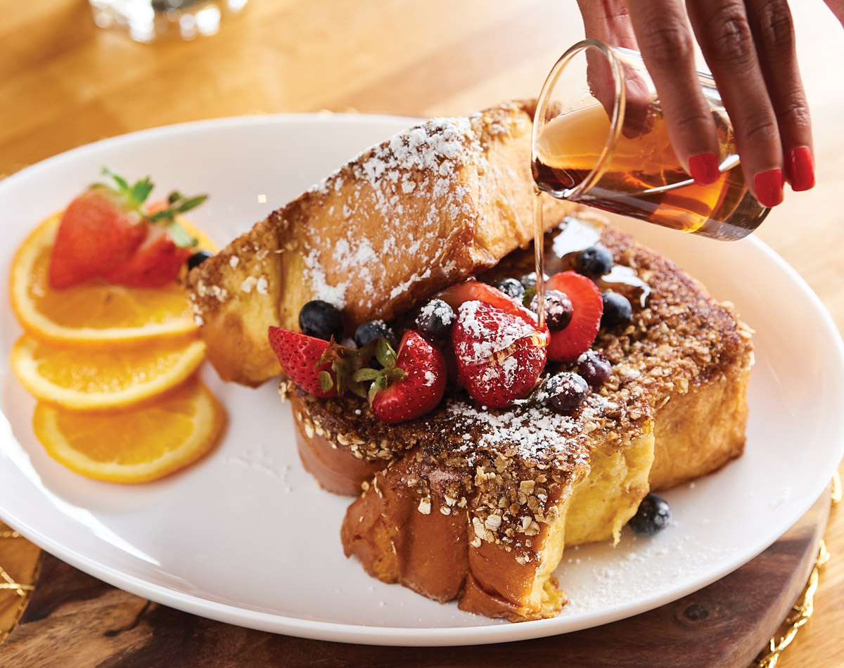 Pouring syrup on top of French toast at Real Milk and Honey