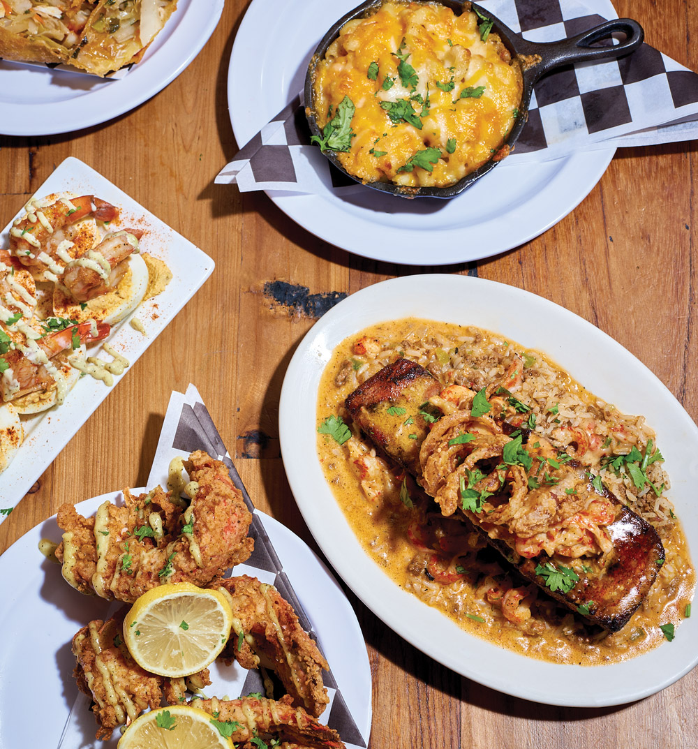 Soul Crab's fried chicken, mac and cheese, and other dishes spread out on a table