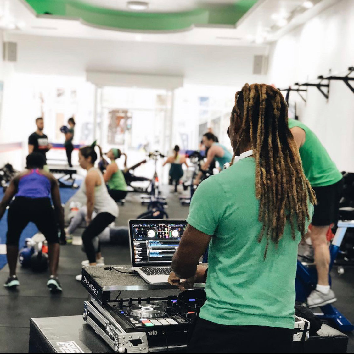 A DJ performs inside a gym as people exercise with kettlebells