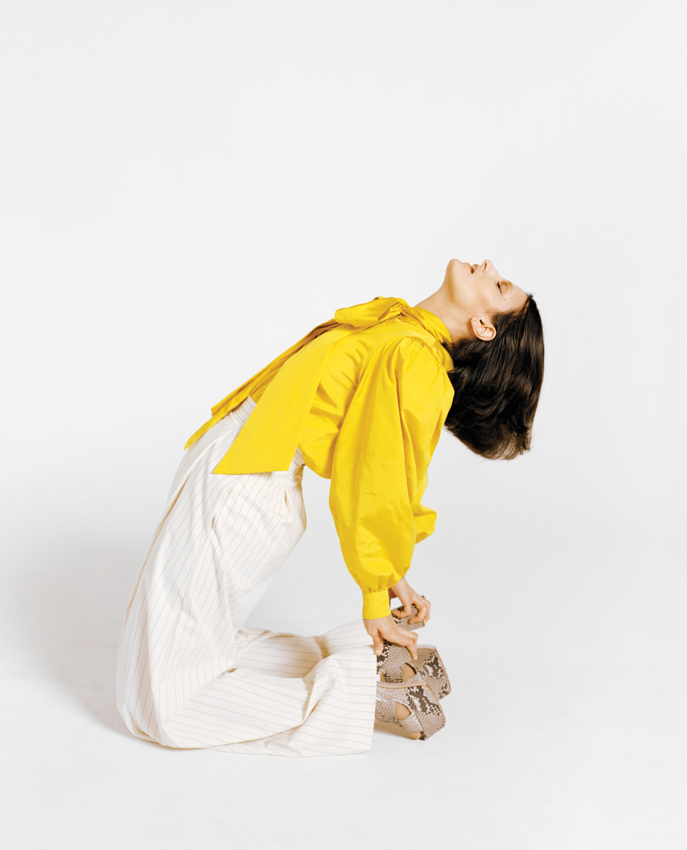 Mattiel Brown in a yellow Tory Burch shirt that has a flowing bow tie on the front